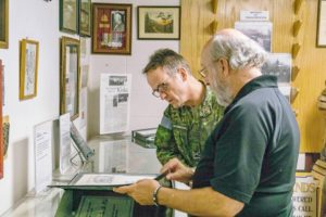Museum Director Ted Leaker discusses a museum artefact with Div Comd.